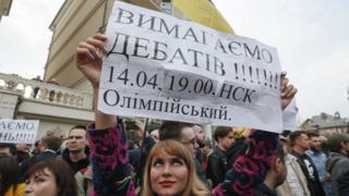 """Активістка з плакатом """"Вимагаємо дебатів"""""""