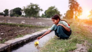 एका मुलीचे पाण्यात होडी सोडतानाचे दृश्य