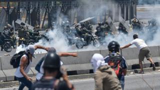 Manifestantes y fuerzas policiales enfrentándose en Caracas, Venezuela.