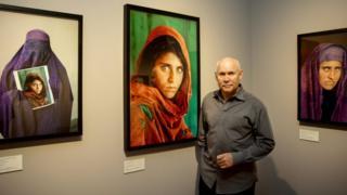 Стив Маккарри на фоне портретов Шарбат Гулы