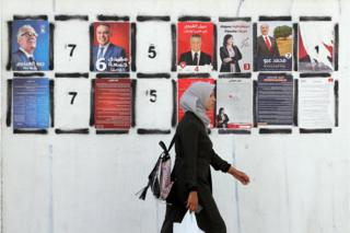 A Tunisian woman walks past posters of Tunisian presidential candidates during presidential campaign in Tunis, Tunisia, 06 September 2019