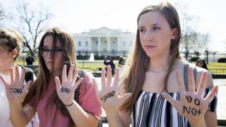 young protesters show their palms, with don't shoot written on them