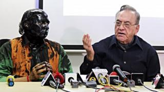 Indian activist Sudheendra Kulkarni (L), whose face was blackened by ink in an alleged attack, looks on as former Pakistani foreign minister Khurshid Mahmud Kasuri speaks to media in Mumbai on 12 October 2015.