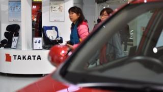 Woman walks past Takata stand