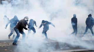 Protesters react amid tear gas during clashes at a demonstration in Paris on 5 December, 2019.