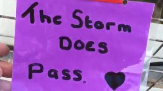 "A note attached to a bridge over a road, which reads ""the storm does pass""."