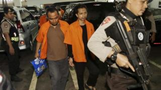 Suspected militants Aprimul Henry (left) and Ahmad Junaedi (right) are escorted by police officers as they arrive for their sentencing hearing at West Jakarta District Court in Jakarta, Indonesia (09 February 2016)