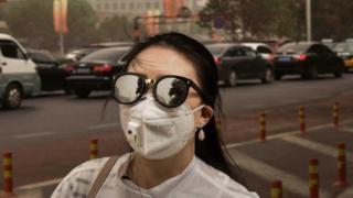 Seorang perempuan berjalan di trotoar kota sambil mengenakan kacamata dan masker.