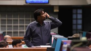 A Pakistani stockbroker watches share prices on monitor during a trading session at the Pakistan Stock Exchange (PSX) in Karachi