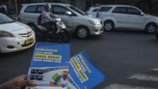 Petugas Badan Pengelola Transportasi Jabodetabek (BPTJ) melakukan sosialisasi kepada pengguna kendaraan bermotor pada hari pertama uji coba perluasan kawasan ganjil genap di persimpangan Pancoran, Jakarta, Senin (2/7), guna mendukung kelancaran arus lalu lintas pada penyelenggaraan Asian Games 2018.