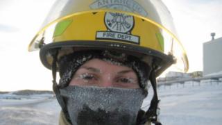 Mujer con un casco del Departamento de Bomberos de Antártica y con las pestañas cubiertas de hielo.