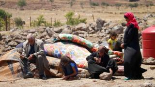 Displaced Syrian civilians from Deraa province wait at a makeshift camp in Quneitra province (22 June 2018)