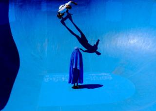The final image in Muir's series showing a woman in a burka standing in a bright blue skate park