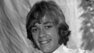 An old black and white photograph of Neil Jones - he has hair down to his ears and frilly light coloured shirt in keeping with the style of the era