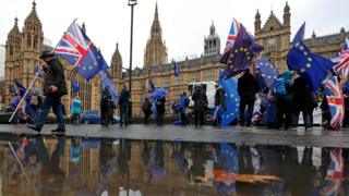 Anti-Brexit demonstrators wave Union Jacks and EU flags opposite the Houses of Parliament on 3 December