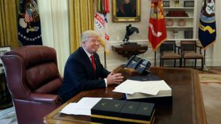 백악관의 대통령 집무실 내 책상에 앉은 도널드 트럼프