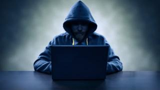 man in hoody with computer