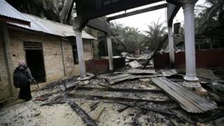 A woman walks next to a burned Church in Aceh Singkil, Indonesia, on 14 October 2015