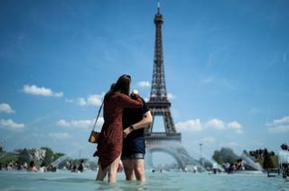 A pair kiss as they chilly themselves down in the fountain of the Trocadero esplanade in Paris on June 25, 2019 with the Eiffel Tower on the background