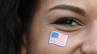 A woman with a US flag sticker on her face