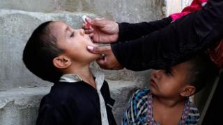 A boy receives polio vaccine drops during an anti-polio campaign in Karachi, Pakistan April 9, 2018