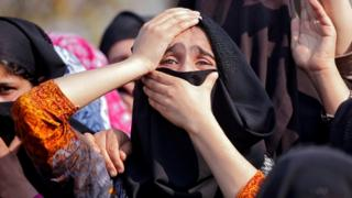 Tearful women with covered heads grieve during a suspected militant's funeral procession