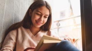 Una joven lee un libro.