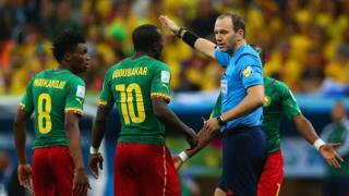 L'arbitre Jonas Eriksson parlant aux camerounais Benjamin Moukandjo et Vincent Aboubakar lors d'un match de Coupe du Monde 2014, opposant le Cameroun au Brésil dans le groupe A.