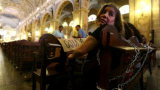 A relative of a victim of human rights abuses under Augusto Pinochet looks back having chained herself to pews at the Cathedral of Santiago on 22 December