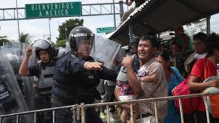 Policial contém imigrantes na fronteira entre México e Guatemala