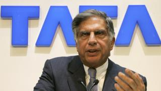 Ratan Tata sitting in front of a Tata sign