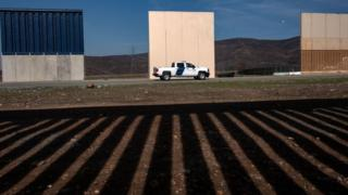 A US Border Patrol vehicle is seen near prototypes for Mr Trump's proposed wall