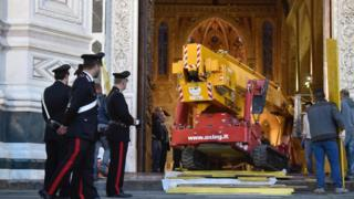crane entering a church as police officers look on
