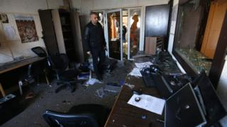 An employee of the Palestinian government-run radio and television stations inspects the damage at one of the studios on January 4, 2019