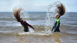Children fipping hair in the sea
