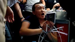 示威者把《環球時報》記者綁起來,做法引起爭議。
