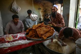 Workers prepare bolani at a roadside stall