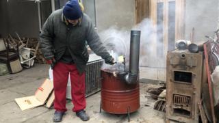 Pastor Tibor Varga with basic barrel stove for migrants