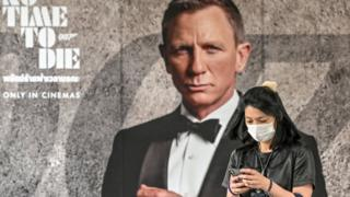 A moviegoer wearing a mask, pictured in front of a James Bond poster
