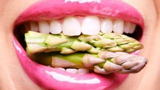 Una boca con espárragos crudos.
