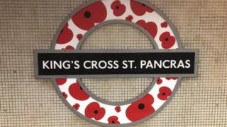 """A London Underground roundel is modified with poppies, at King""""s Cross St Pancras station"""