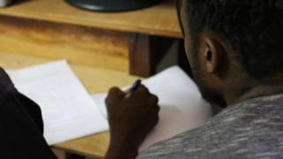 Haitiano sentado perto de documentos sendo assinados