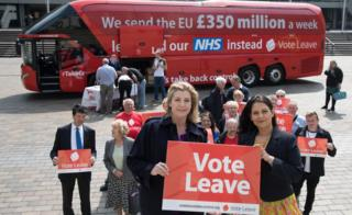 "Vote Leave campaigners with a campaign bus behind them that says ""We sent the EU £350 million a week"""