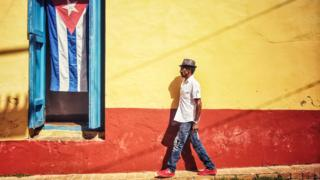 A man walks past a Cuban flag in Trinidad
