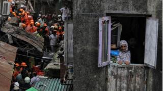 A resident looks out of her house as rescue workers search for survivors at the site of a collapsed building in Mumbai, India, July 16, 2019