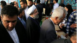 Hassan Rouhani surrounded by people during a polling station