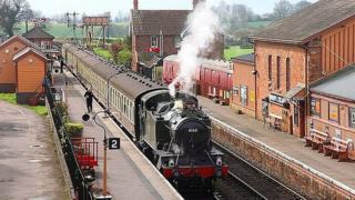 Steam train going through West Somerset Railway line.