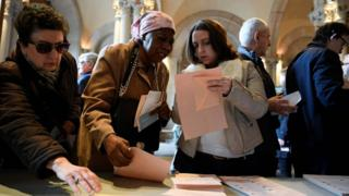 Voters pick their ballots at the Central University of Barcelona being used as a polling station in Barcelona