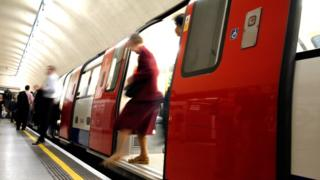 People departing Tube train in station