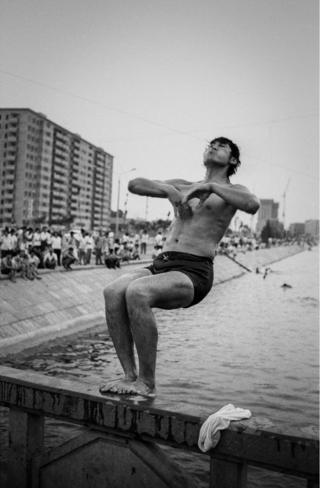 A man jumps backward into the sea